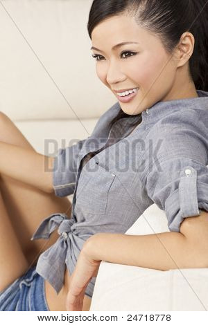A beautiful sexy young Chinese Asian Oriental woman with a wonderful toothy smile relaxing on a sofa in denim jeans shorts