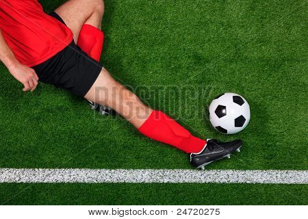 Overhead photo of a football or soccer player sliding in to save the ball going over the sideline