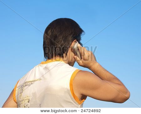 Back Of Young Man With Mobile Phone