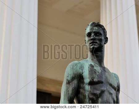Bronze Statue Of A Athletic Male Body In Front Of A Greek Temple