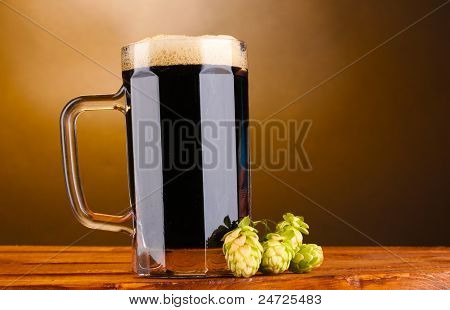 dark beer in a mug and green hop on wooden table on brown background