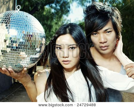 Attractive young couple holding disco mirror ball. Image cross processed