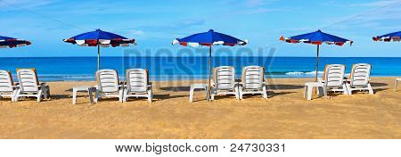 Sunbeds And Umbrellas On A Tropical Beach