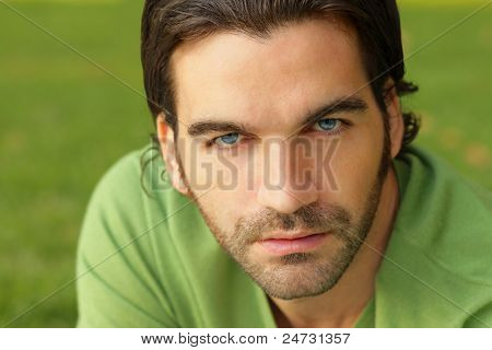 Close up portrait of a good looking male model in green sweater against natural green background