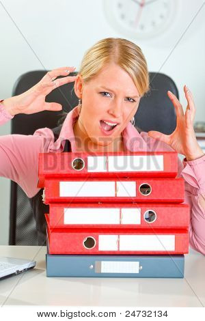Stressed Modern Female Manager With Pile Of Folders At Office Desk