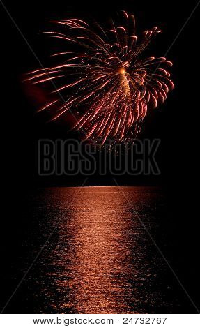 Long Exposure Of Fireworks Reflecting On Calm Rippling Water