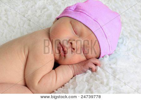Newborn baby girl asleep on a white blanket.