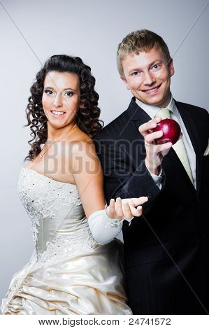 Groom Taking Red Apple From Young Beautiful Bride