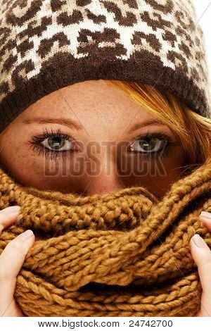 young redhead woman hiding behind scarf
