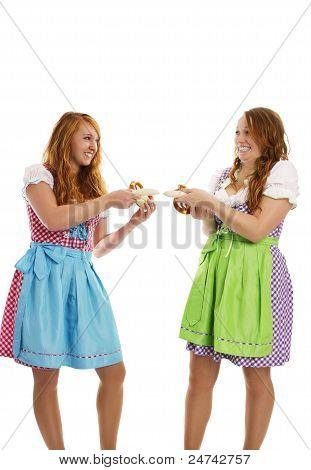 zwei Bayerische gekleidete Mädchen ziehen an Kalbfleisch Würste