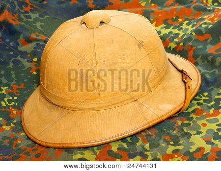 Retro helmet for tropical destination on a camouflage fabric.