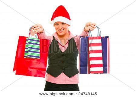 Smiling Modern Business Woman In Santa Hat Presenting Shopping Bags