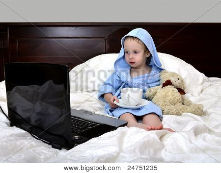 Little Girl In A Bathrobe Relaxing On The Bed After A Shower With Cup Of Tea And Laptop