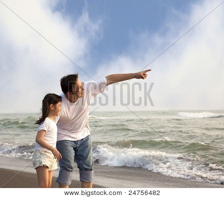 father pointing and little girl looking it on the beach