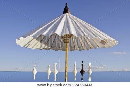 White Umbrella And Chessmans On Mirror