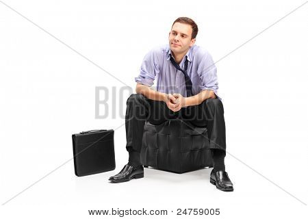 A studio shot of a disappointed businessman sitting isolated on white background