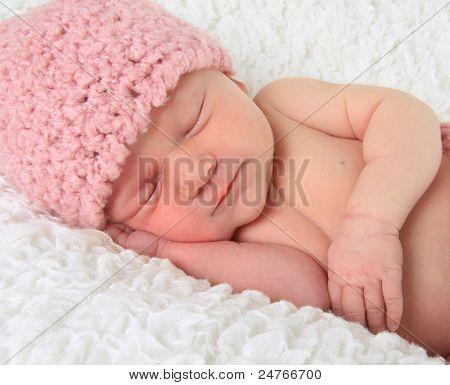 Niña bebé dormida sobre una manta.