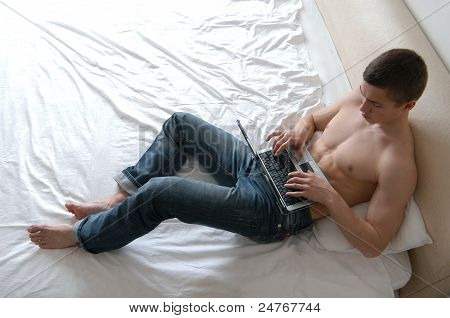 Shirtless Man Working On A Laptop