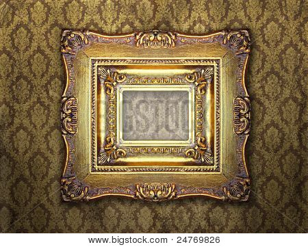 Ornamental gold frame on an aged damask wallpaper