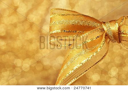 Shiny gold metallic bow against background of shimmery gold fabric (defocused) with copy space.