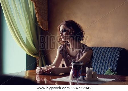 Fine art photo of a gorgeous brunette woman sitting alone near a window