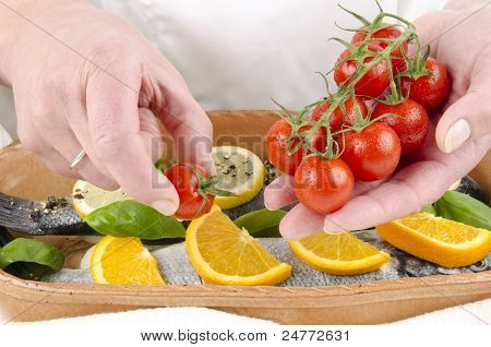 Female Chef Covered Sea Bass With Orange Slices, Lemon Slices And Tomato