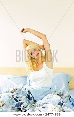 Happy Young Woman Waking Up In Bed