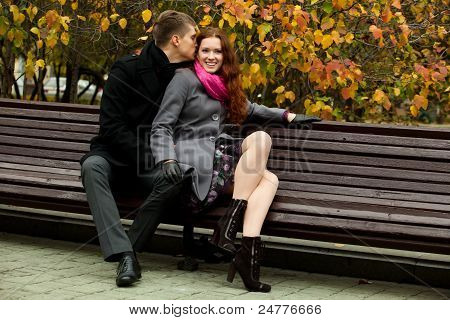 Young Man Says Something In Ear Of A Woman