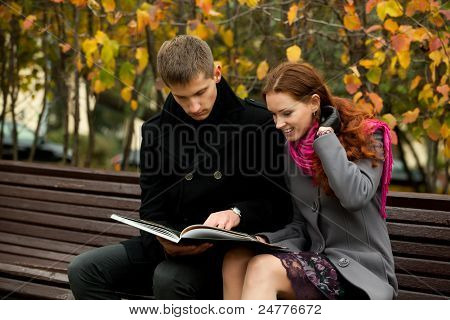 Young Couple On Bench And Read Book