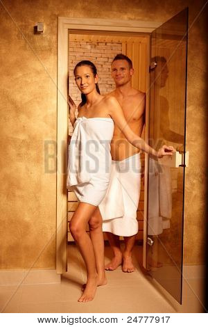 Couple standing at sauna door, smiling after relaxing in steam, leaving.?