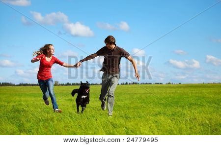 Young happy family running with dog on a green meadow