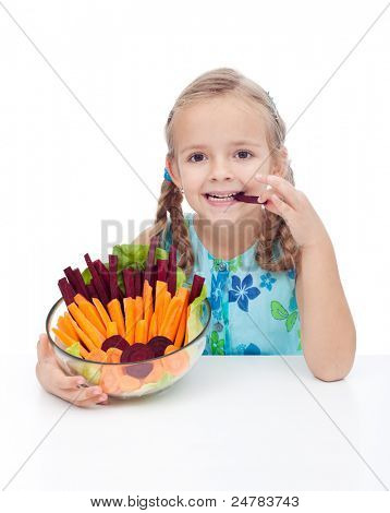 Little girl holding bowl of vegetables and munching beetroot and carrot