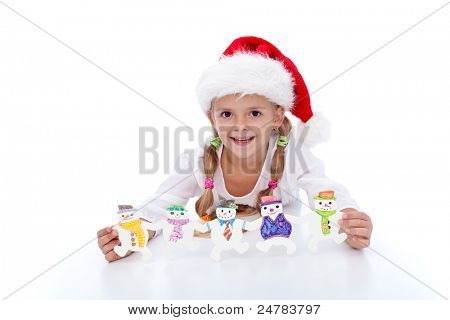 Happy girl at christmas time with handmade decoration and santa hat