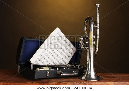 antique trumpet and clarinet in case on wooden table on brown background