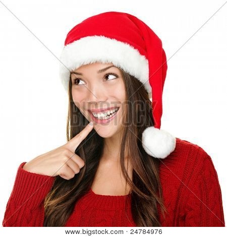 santa christmas woman looking to the side thinking happy and playful. Asian christmas girl wearing santa hat and red sweater isolated on white background.