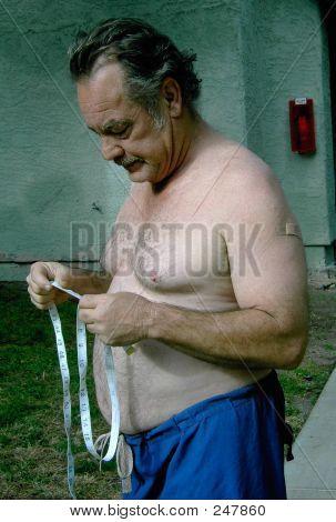 Man Contemplating Tape Measure