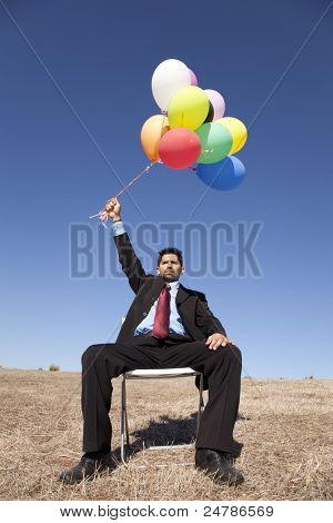 Businessman sitting in a chair at a field holding colorful balloons