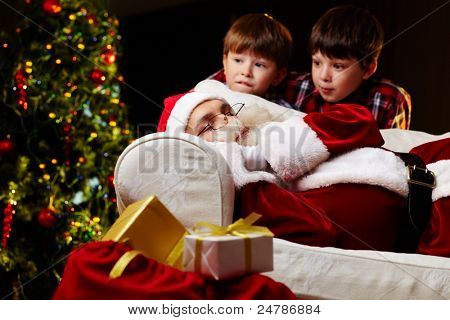 Photo of Santa Claus sleeping on sofa with two amazed kids near by