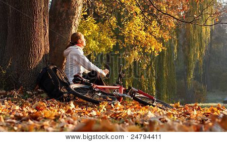 Woman Cyclist Relaxing Illuminated By The Rays Of The Rising Sun