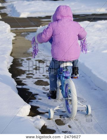 Child Riding Bike In The Snow