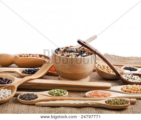 Mix from different beans, legumes, peas, lentils in spoon on the sackcloth on white