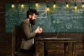Man With Long Beard With Computer On Chalkboard. Bearded Man Work On Laptop In Classroom. Businessma poster