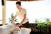 Female massage therapist giving a massage at a spa poster