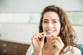 Portrait Of Beautiful Patient Holding Orthodontic Retainers In Dental Clinic poster