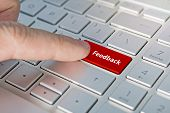 A Finger Press Blue Feedback Button On Laptop Keyboard. Feedback Inscriptions On The Grey Silver Key poster