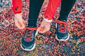 Healthy sport woman trail runner tying laces of running shoes. Athlete girl getting ready for run wo poster