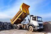 stock photo of dump  - A dump truck is dumping gravel on an excavation site - JPG