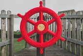 Red Wooden Steering Wheel Of A Wooden Ship On Childrens Playground poster