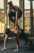 Man And Woman In Sportswear In Gym, Window On Background. Couple Does Acroyoga, Physical Practice Of poster