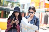 Portrait Of Traveler Woman Find The Way With Friend Together In City. Asian Women Using Map To Find  poster